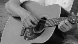 Mann zupft Gitarre um zu zeigen wie das aussieht zum Gitarre spielen lernen