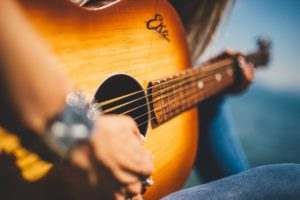 Mann schlägt Gitarre um zu zeigen wie das aussieht zum Gitarre spielen lernen